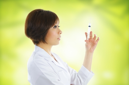 one female: Asian beautician with syringe on green background