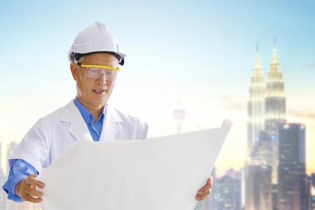 Senior Asian engineer with blueprints standing outside modern building photo