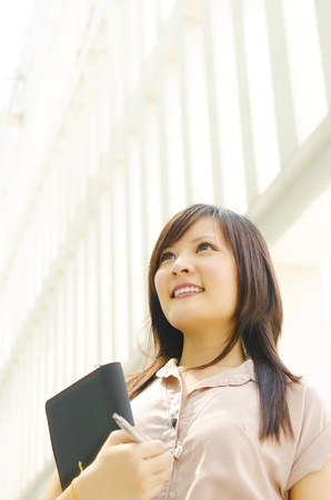 bright future: A young Asian woman looking far away to bright light in front of a modern office building, with diary on hand. Stock Photo