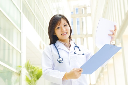 Young female practitioner doctor holding a writing pad\ standing inside hospital
