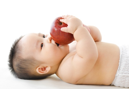 Pan Asian baby boy eating red apple on bed photo