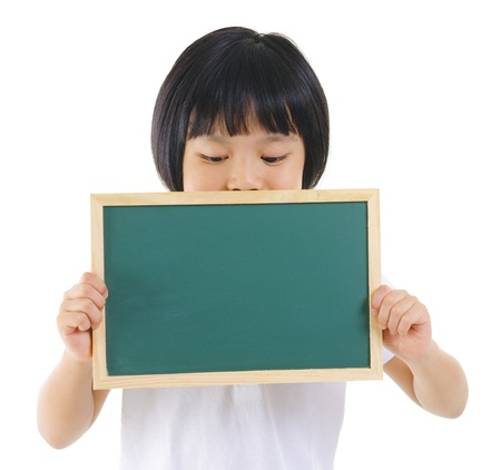 7 years old pan Asian school girl covered her mouth with blackboard on white background photo