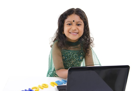 infant school: Little Indian girl using a laptop on table, isolated on white background Stock Photo