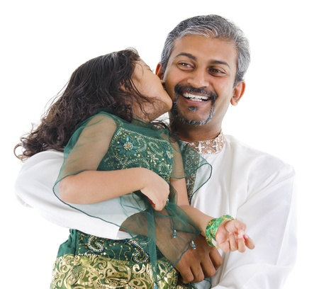 Happy little Indian daughter kissing her father on white background photo