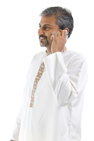 Mature traditional Indian man talking on mobile phone, isolated on white background photo