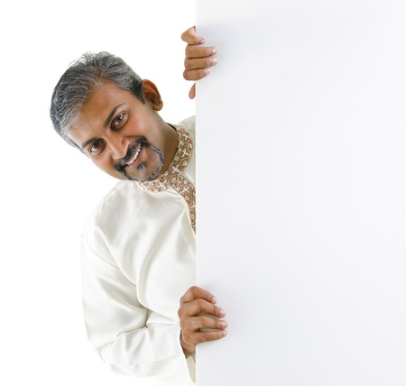 Mature traditional Indian male hiding on a blank space. photo