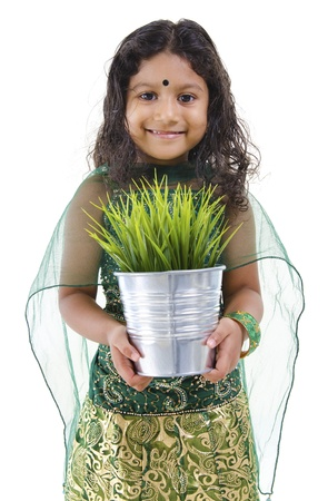 Concept of little Indian girl holding a plant on white background photo