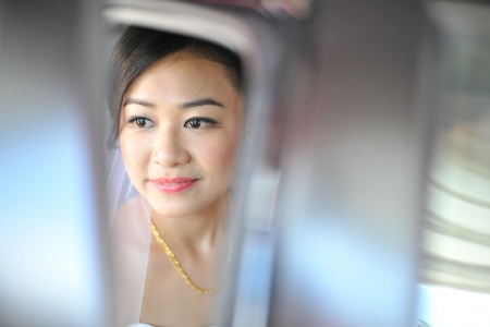 Asian bride looks out of the car photo
