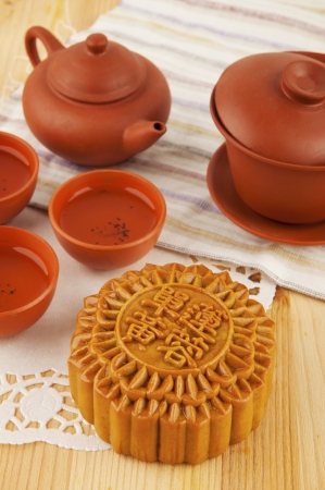 moon cake festival: Mooncake and tea set on table. Mooncake traditionally eaten during the Mid-Autumn Festival. Chinese word on mooncake means single yolk lotus paste Stock Photo