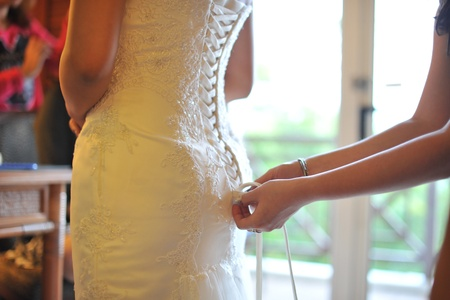 Wedding preparation, wedding gown being tied up Stock Photo
