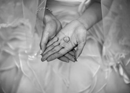 Wedding ring on bride palm, monotone photo