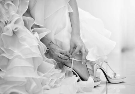 bridal gown: La novia est� poniendo en sus zapatos para el d�a de la boda. Foto de archivo