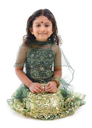 Young little Asian Indian girl smiling and sitting on white background photo