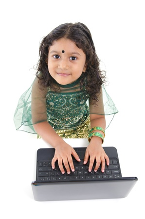 Little Indian girl using a laptop on table, isolated on white background photo