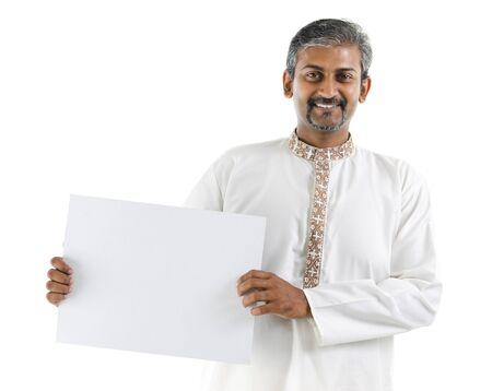 kurta: Mature Asian Indian businessman holding a white board standing over white background