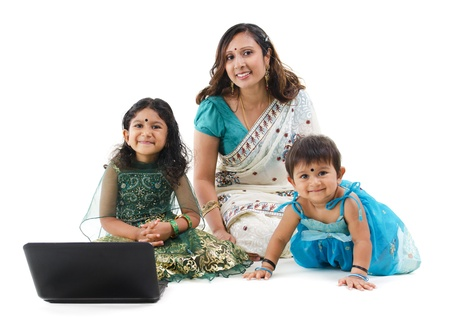 Traditional Asian Indian family using laptop computer over white background photo