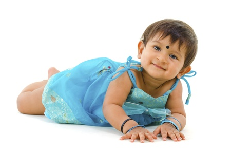 Adorable 10 months old Indian baby girl lying over white background photo