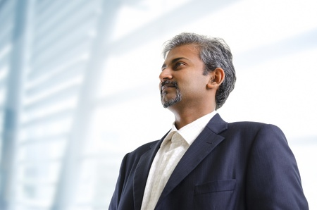 Mature Asian Indian businessman looking away standing on office background photo