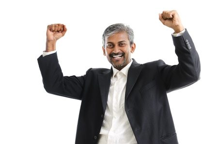 Portrait of excited Asian Indian businessman celebrating success over white background photo