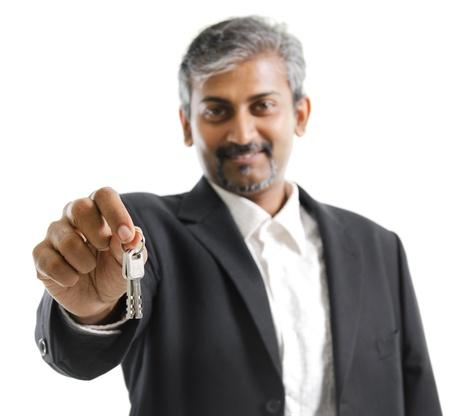 Mature adult Asian Indian man arm out holding a new key over white background photo
