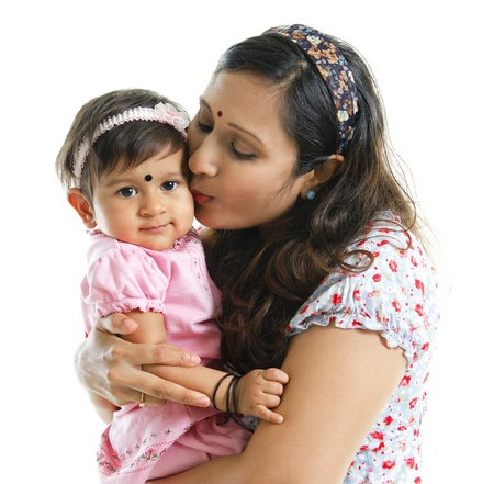 Asian Indian mother kissing her baby girl, isolated on white background photo