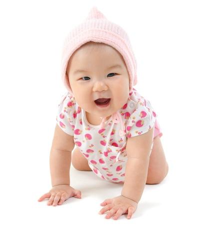 bebe gateando: Bebé de seis meses niña de rastreo sobre fondo blanco Foto de archivo