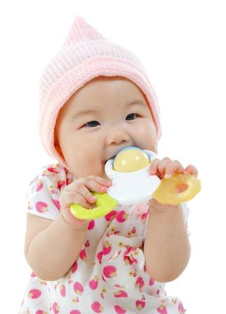 playing with baby: Bella gara mista bambina asiatica mordere con i suoi giocattoli. Archivio Fotografico