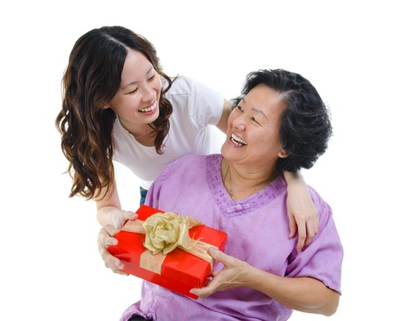 receiving: Happy Mixed race Asian mother receiving present from her daughter