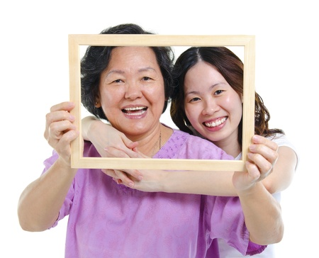 Mixed race Asian senior mother and adult daughter looking fun through an empty frame photo