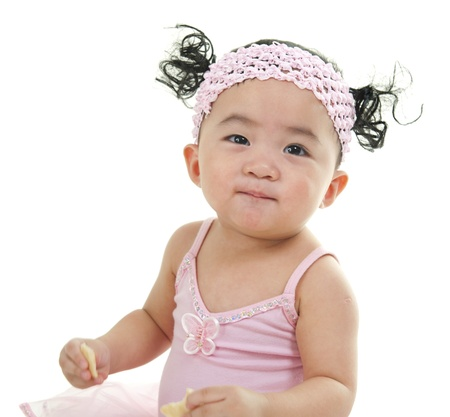 One year old cute pan Asian baby girl eating on white background photo