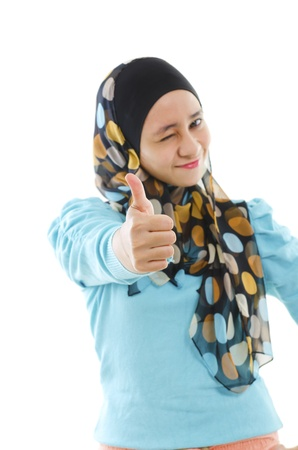 perfect sign: Cute young Muslim girl giving a thumb up sign over white background