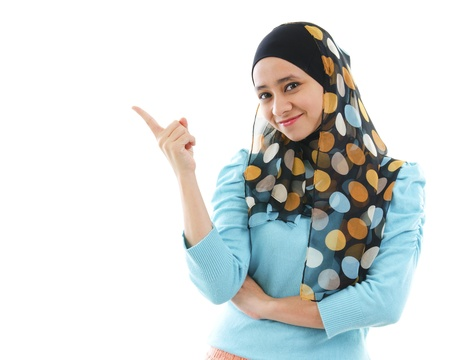 arab: Cute young Muslim woman pointing on empty space, isolated on white