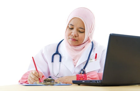 Muslim female doctor writing report on her working desk photo