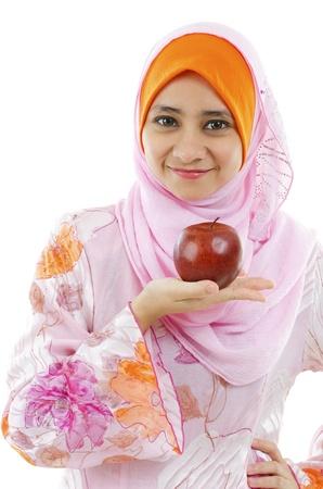 femme musulmane: Jeune femme musulmane tenant une pomme sur la paume, le concept saine alimentation