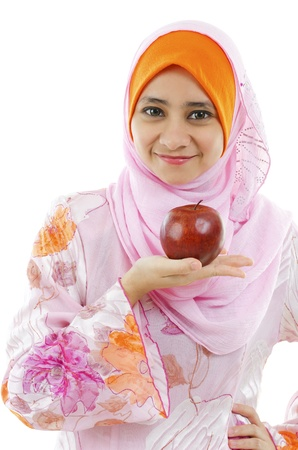 Young Muslim woman holding an apple on palm, healthy eating concept photo