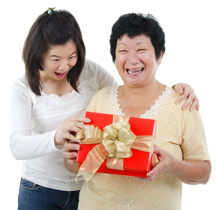 Asian senior women surprises to receiving a present, over white background photo