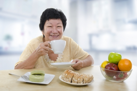 Asian senior woman having breakfast at home photo