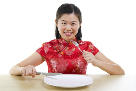 Asian oriental woman holding fork and knife with an empty plate ready for food, isolated on white background photo