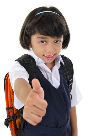 Thumb up Southeast Asian primary school girl with backpack on white background photo