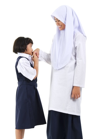 Young Southeast Asian Muslim girl  greeting to her elder sister over white background photo