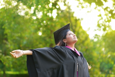higher: Young Asian Indian female student open arms outdoor on graduation day