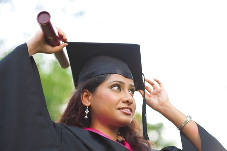 academic robe: Young Asian Indian female student adjusting her graduate hat