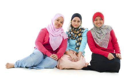 mujeres musulmanas: Retrato de tres mujeres que se sientan alegres musulmanes en el fondo blanco