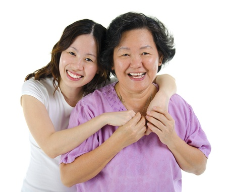 white women: Happy Asian senior mother and adult daughter over white background Stock Photo