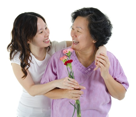 Young Asian girl carnation flower to her mum, over white background photo