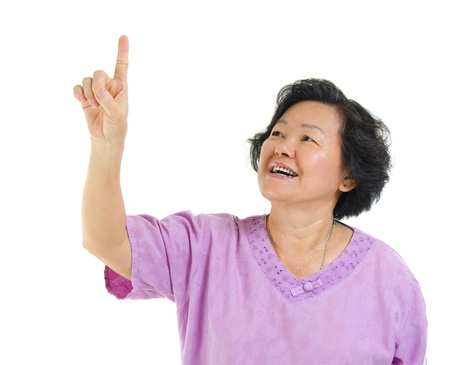 60s Asian senior woman pointing on transparent virtual screen button, over white background photo