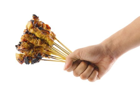 Asian man hand holding a bunch barbecued satay chicken over white background photo