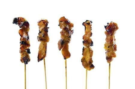 Five satay chicken sticks over white background photo