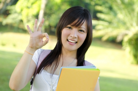 okay sign: Cheerful Asian university student giving an okay hand sign Stock Photo