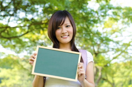 asian people: Young Asian college girl holding a blackboard outdoor, green park Stock Photo